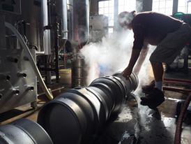 Picture inside the brew house. Morning sun coming thru large rectangular brew house windows. Head brewer Donny Abraczinskas is bent over cleaning a metal firkin. Theres steam rising thru the sunlight up towards him. Other firkins are lined up in the foreground along with the brew hub control panel to the left.